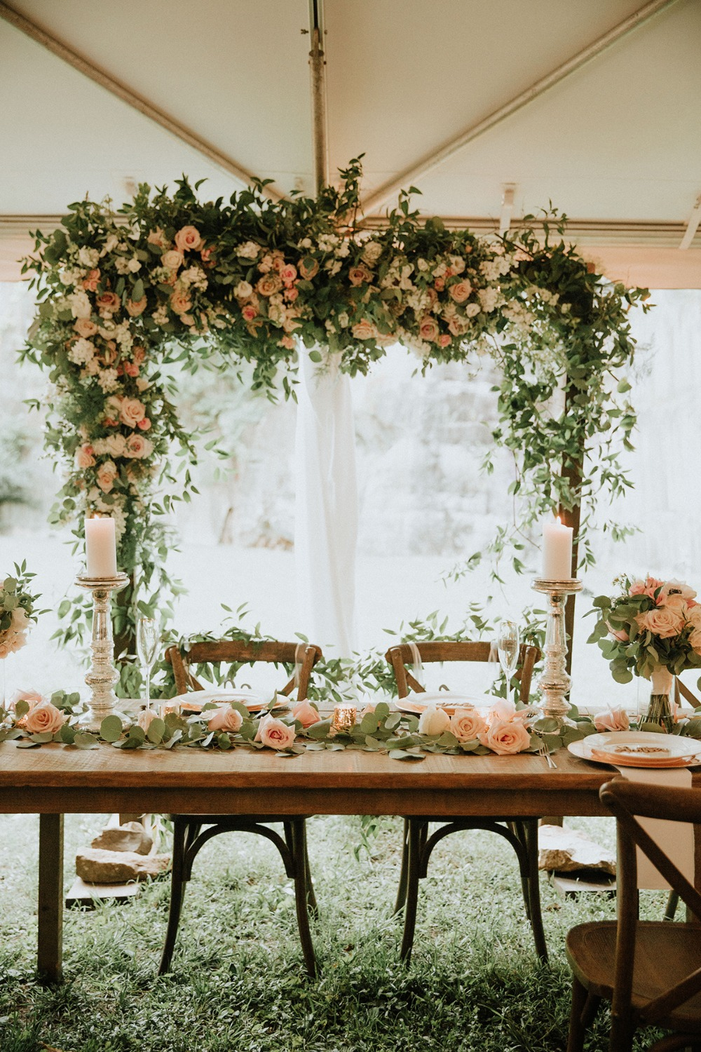 wedding arch behind the sweetheart table