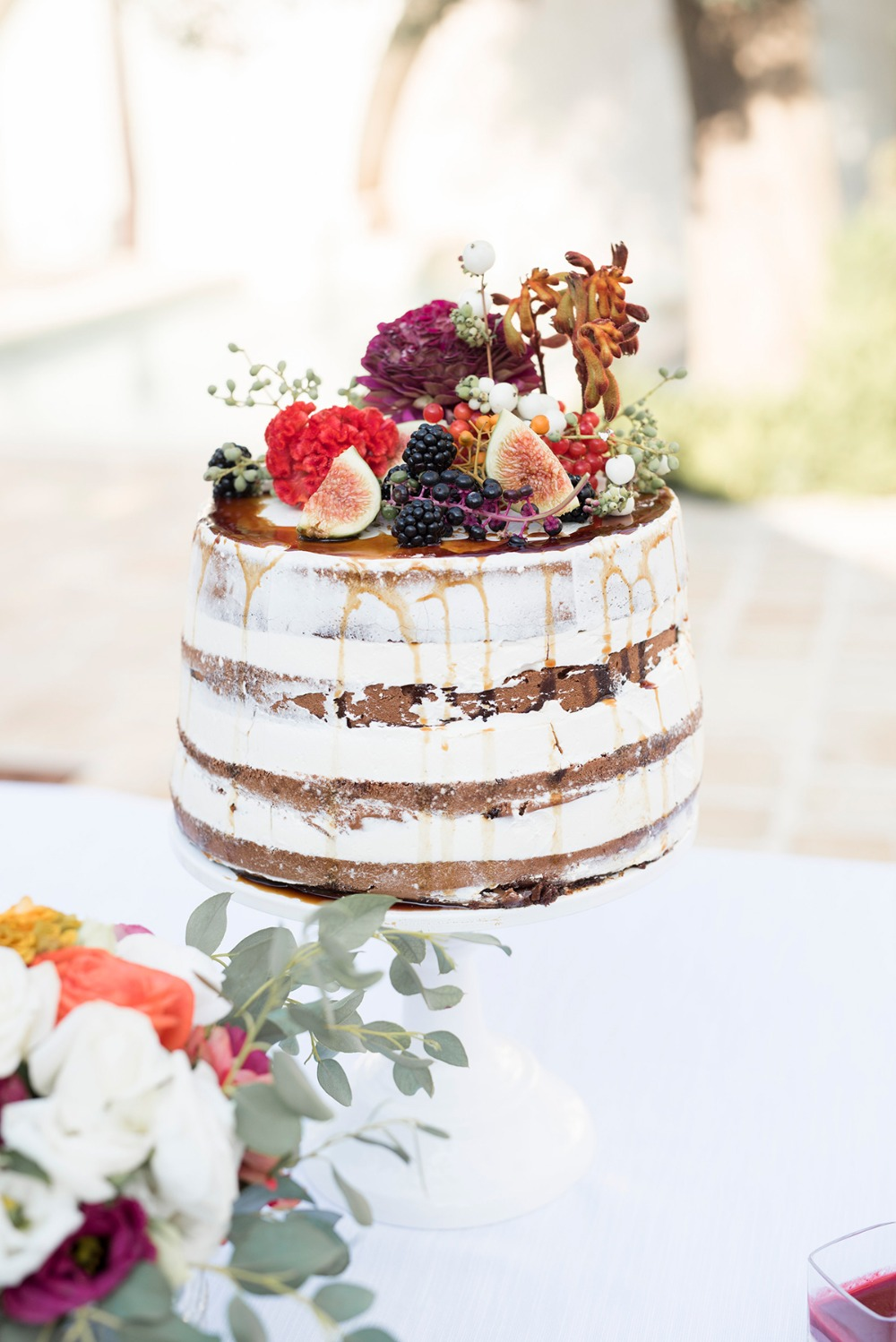 nearly naked wedding cake with fruit and floral top