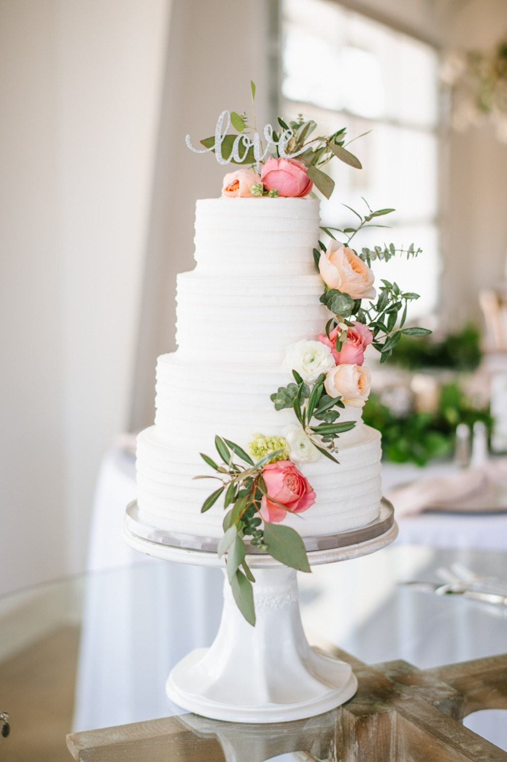 wedding cake with flower and greenery accents