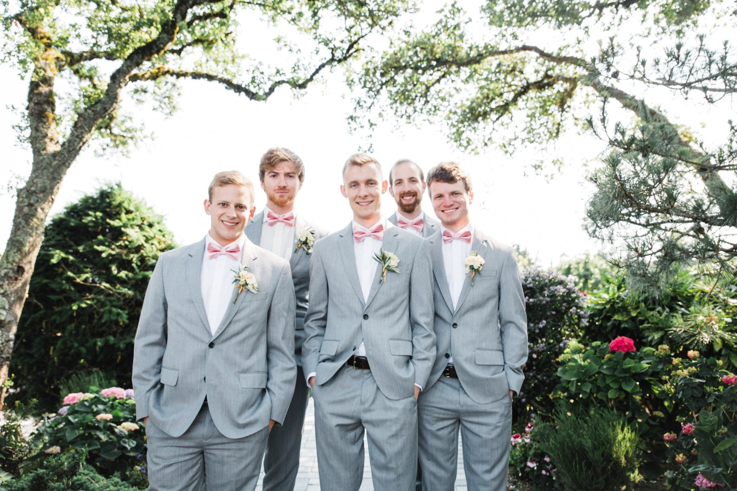 groomsmen in grey suits with pink bowties