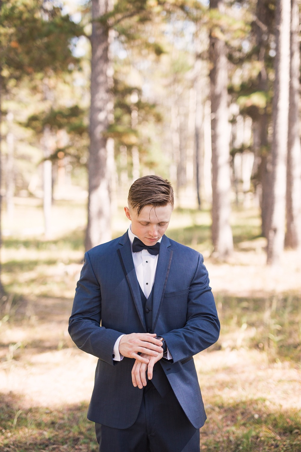 groom in three piece navy suit