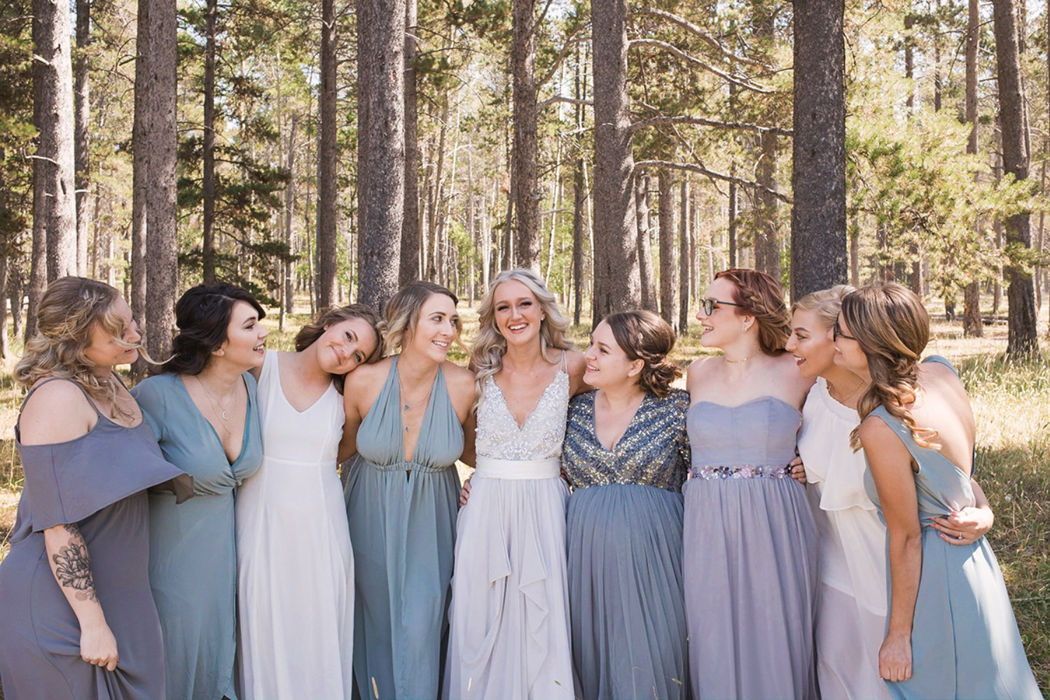 bride and her bridesmaids in mismatched blue