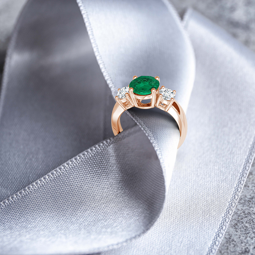 The round GIA certified emerald prong set at the center exudes a sparkling rich green hue. Prong set white diamonds flanking the center