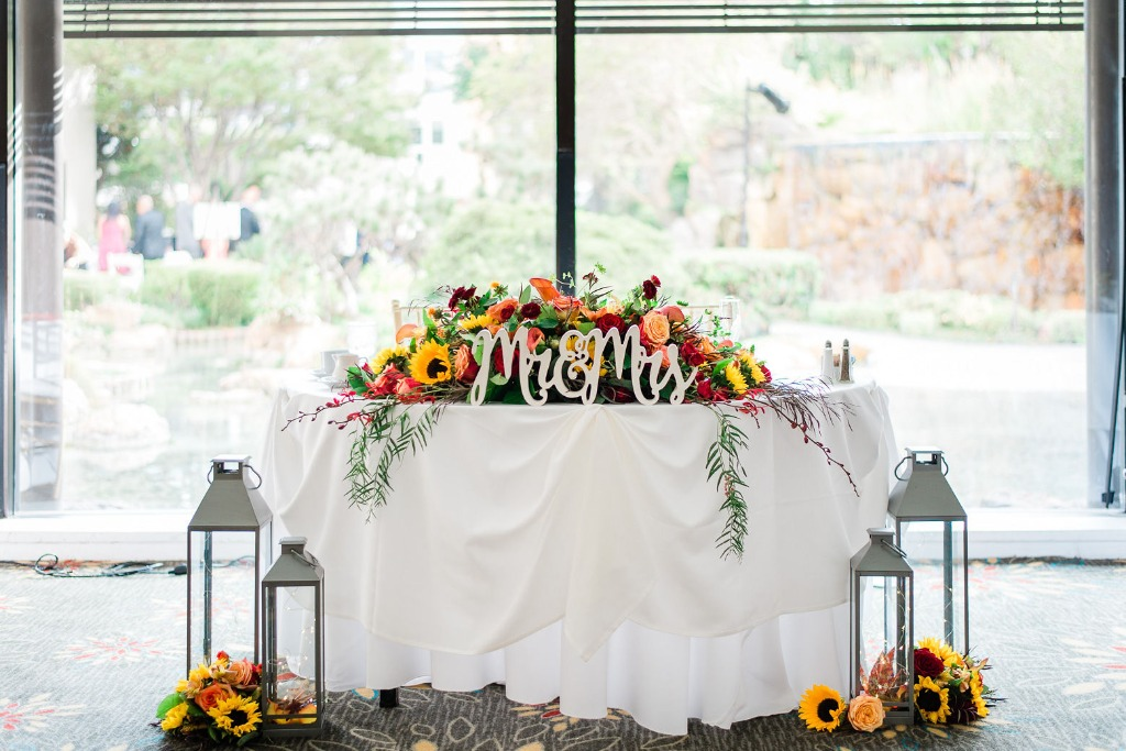 This sweetheart table was adorned with festive fall-colored florals that brought in a beautiful pop of color to contrast the traditional