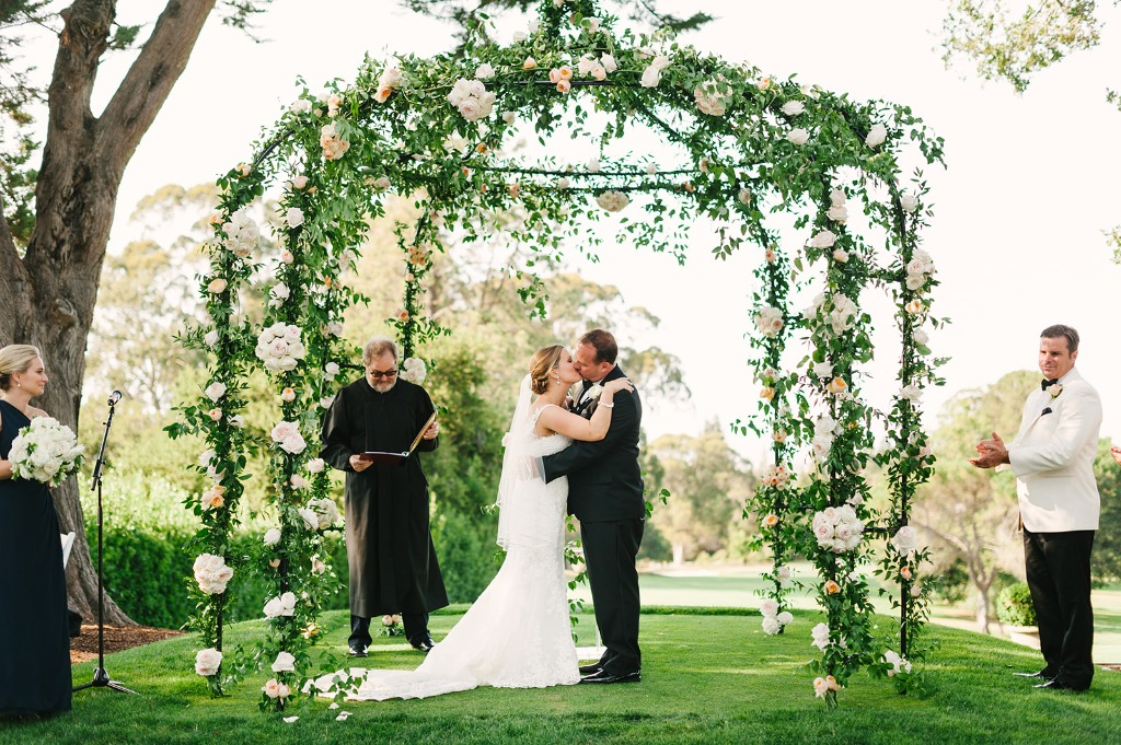 Outdoor wedding ceremony under dramatic wrought iron arch covered in garden roses.