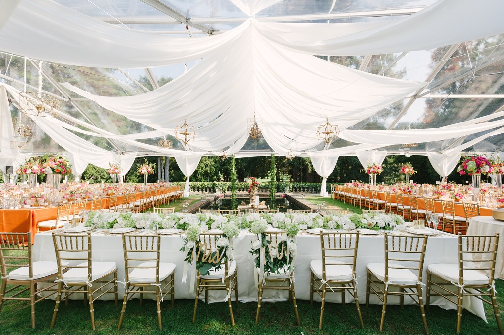 Tented wedding reception with fountain. Orange, pink and dove gray. Roses, hydrangea.
