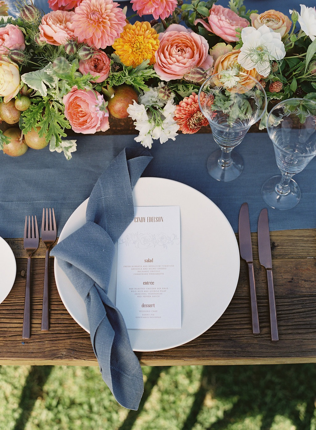 Farm table place setting. Blue linen napkin, Coral, peach and yellow centerpieces with fresh fruit. Outdoor reception.
