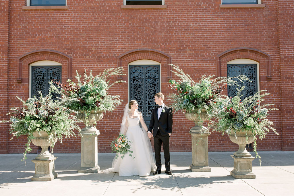 Wedding Ceremony, Brick Backdrop. Large Urns of Greenery. Outdoor Ceremony.