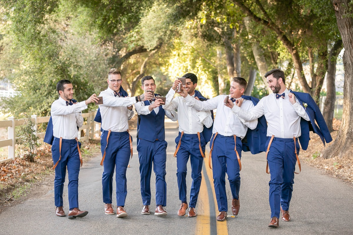 groom and his groomsmen in blue suits and suspenders