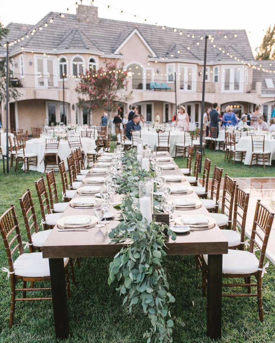 Backyard wedding with farm tables and floral garlands