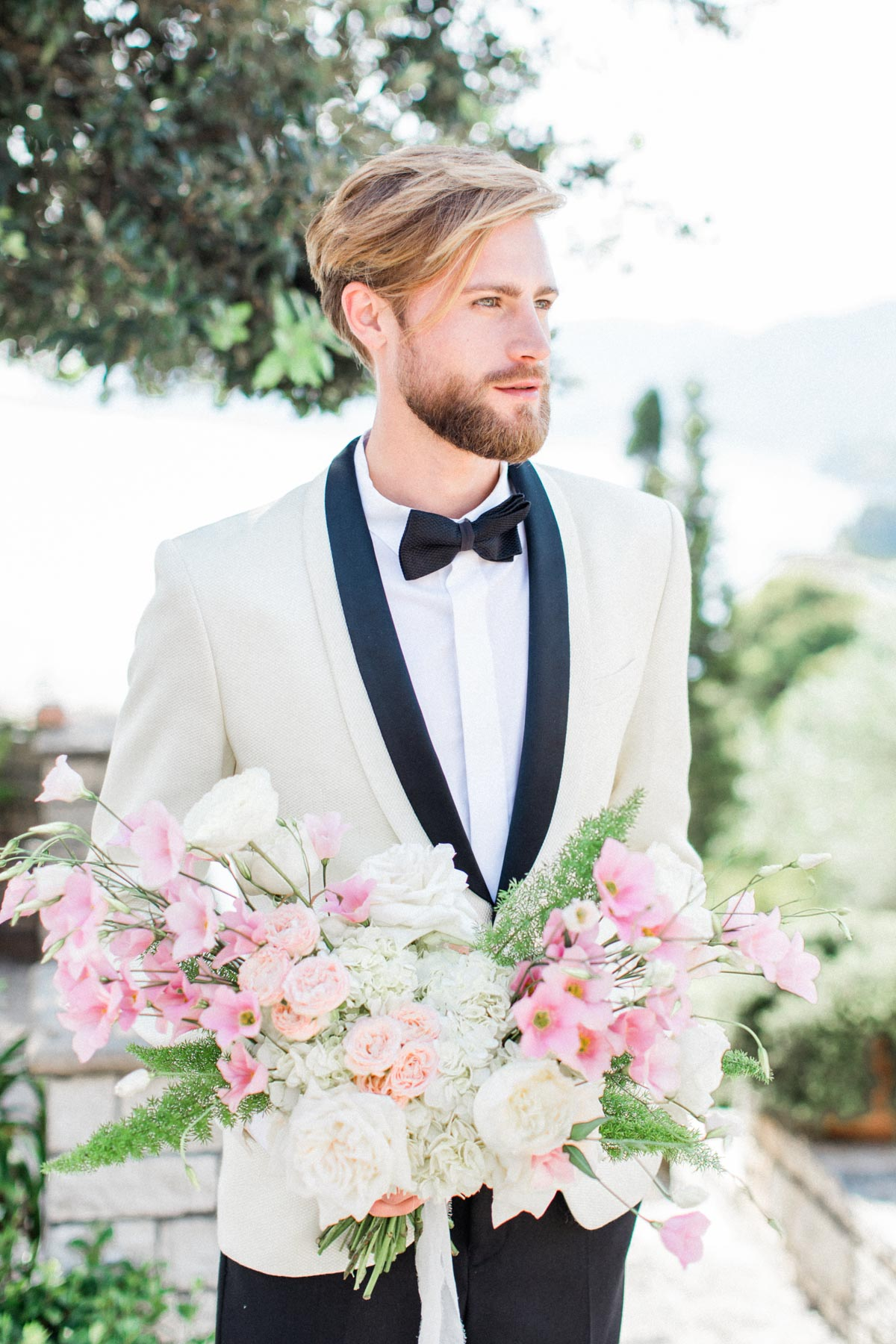 groom in white dinner jacket and black bow tie