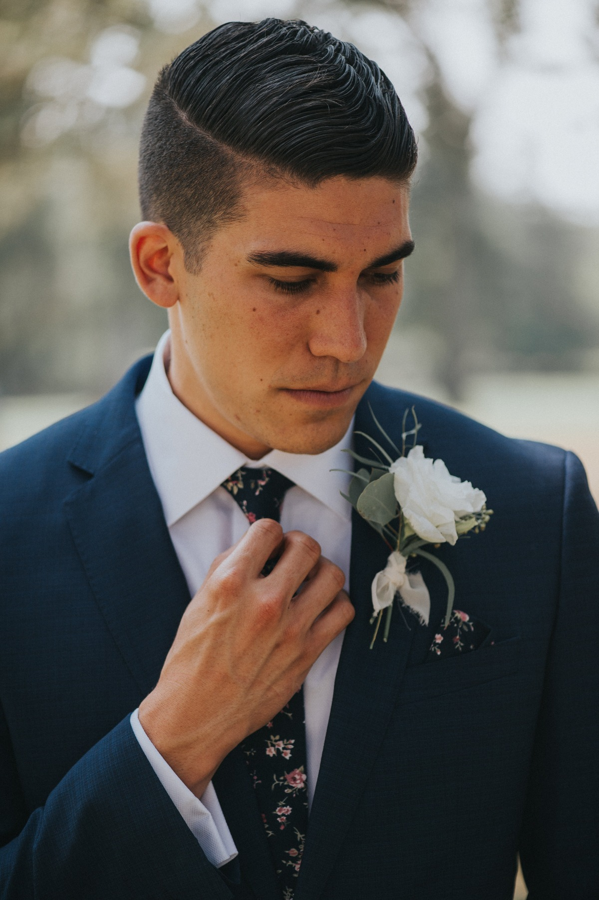 groom in navy suite with floral tie and pocket square