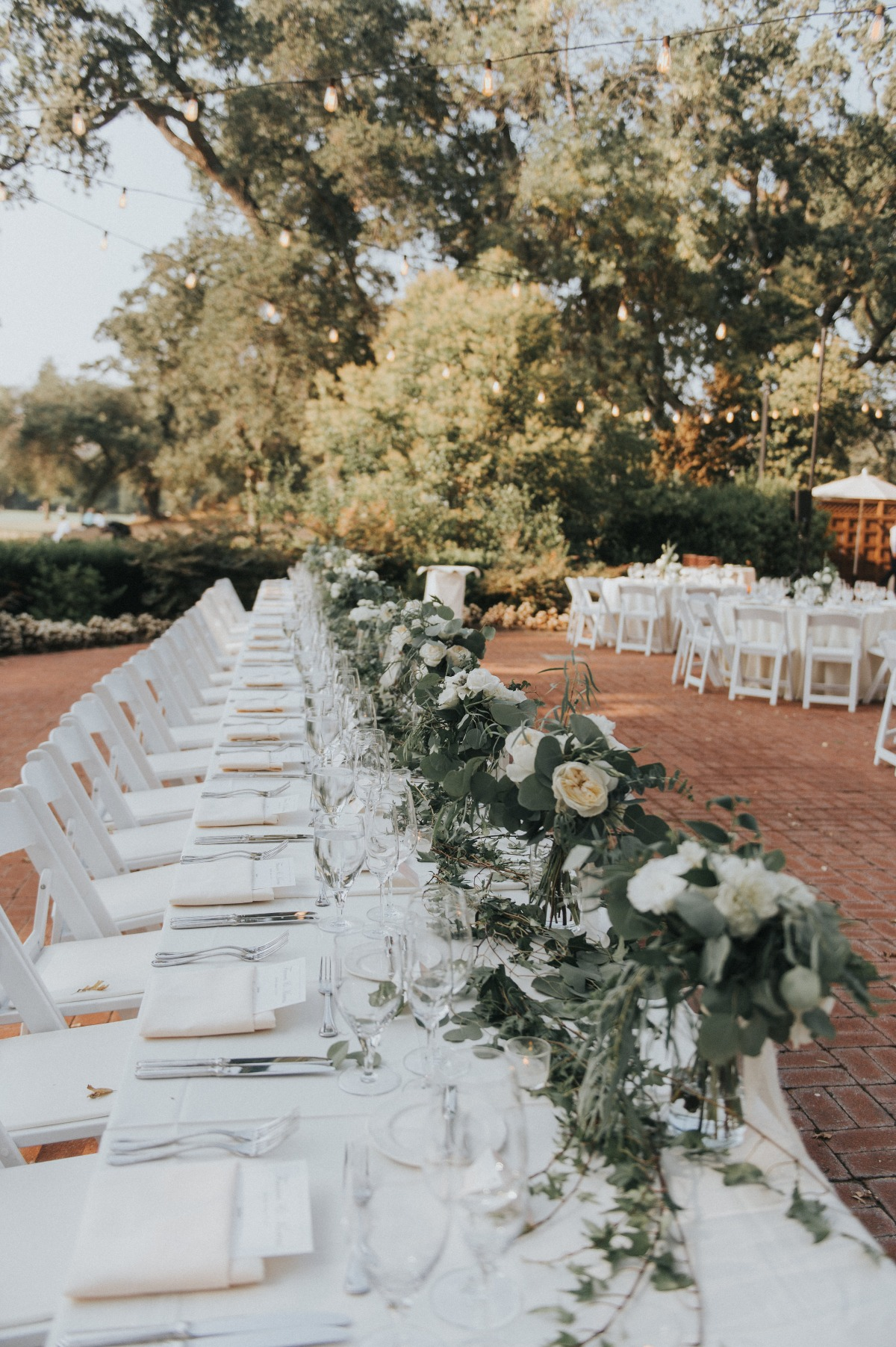 wedding party family style seating with white and greenery floral decor