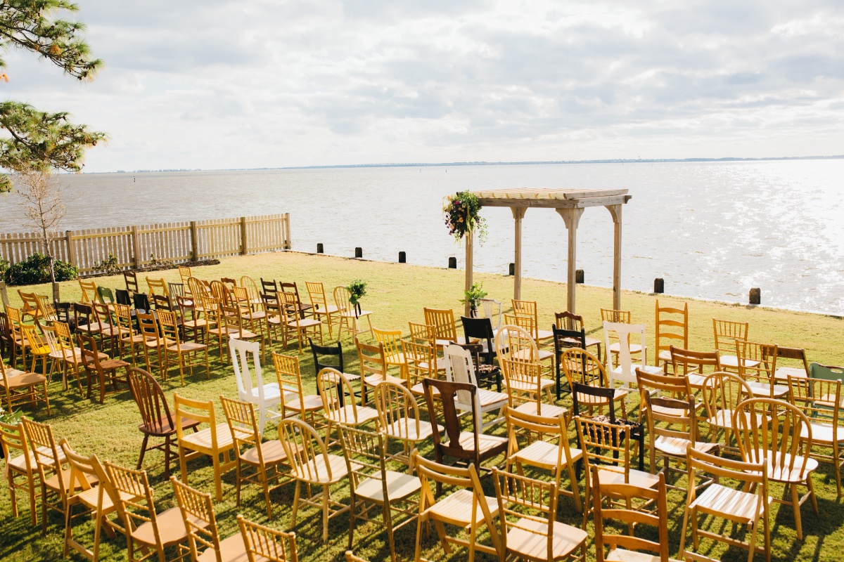 Rustic waterfront ceremony with mismatched chairs