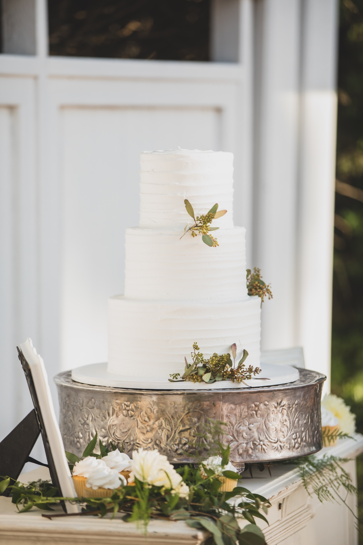 Simple buttercream wedding cake with seeded eucalyptus