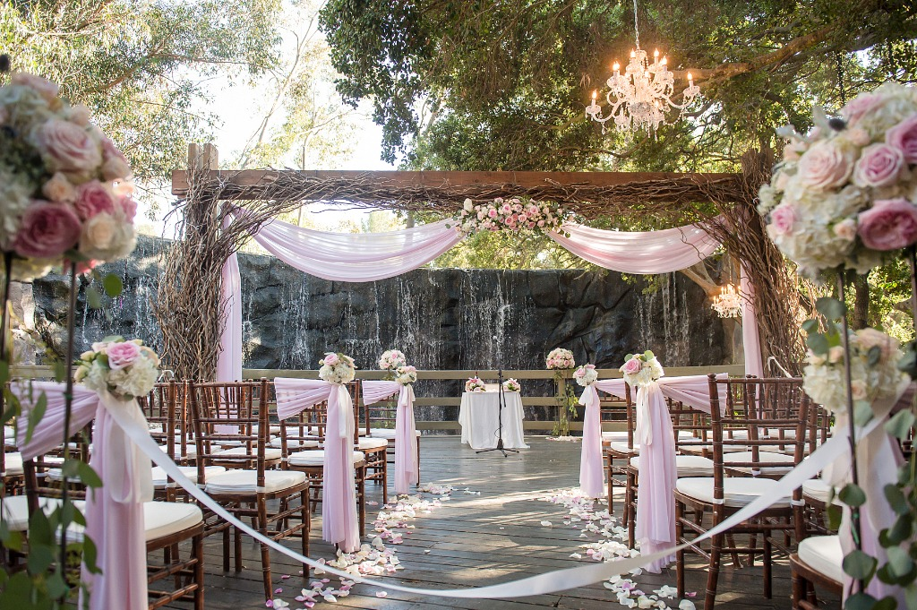 How romantic is this ceremony location? We love the waterfall in the background and the beautiful wooden arch that blends together