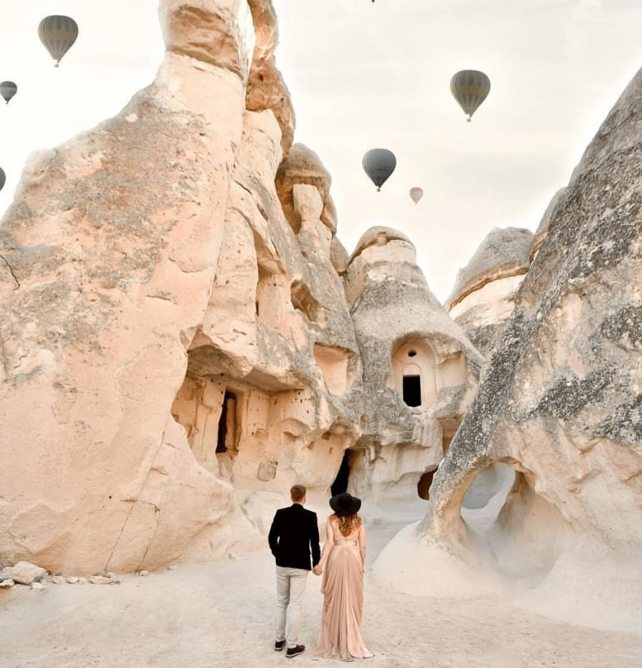 Engagement photos in between sand/mountain huts with hot air balloons