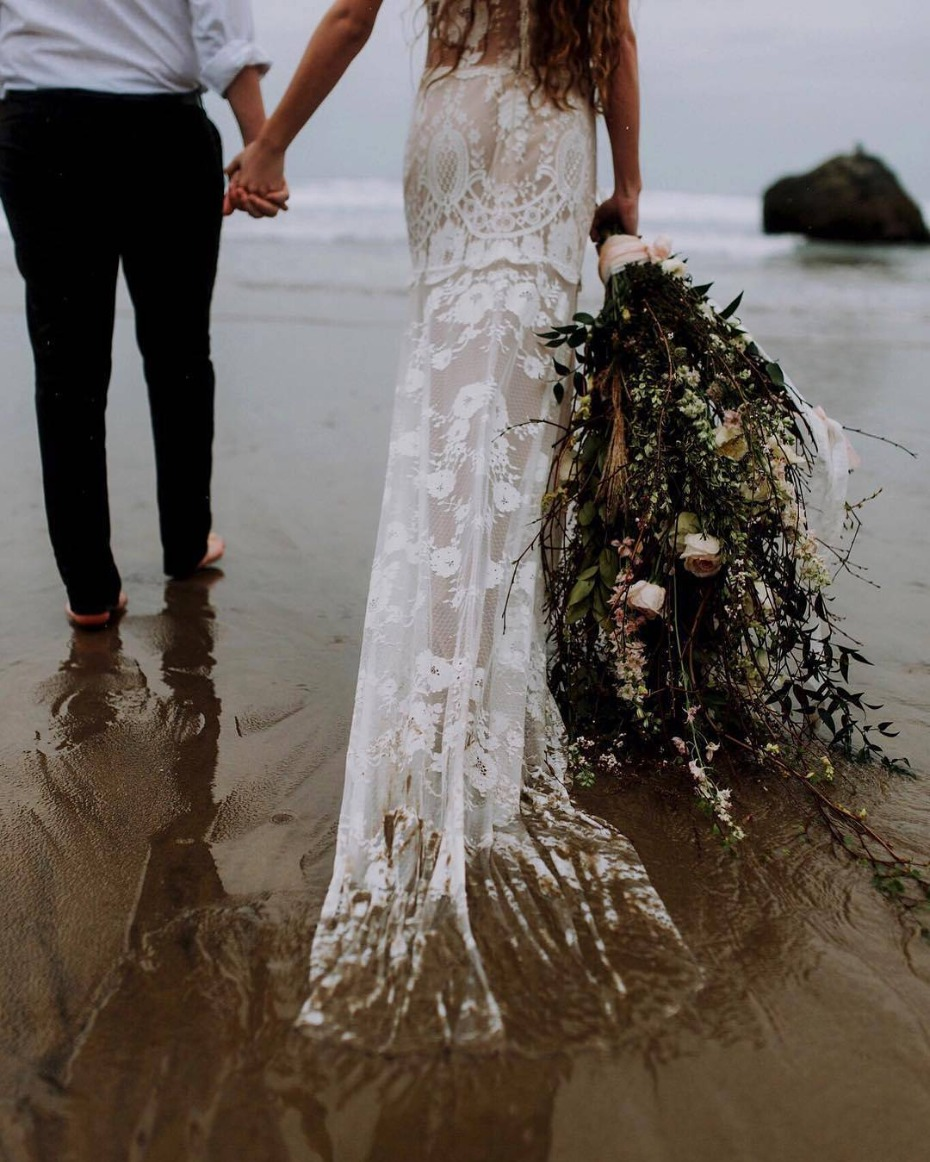 Bride holding a huge bouquet as she walks into the ocean
