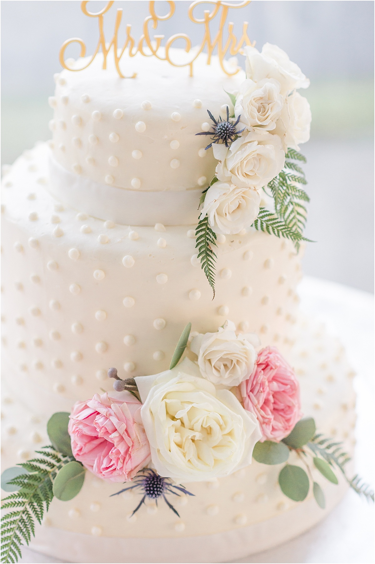 white and pink floral accented cake