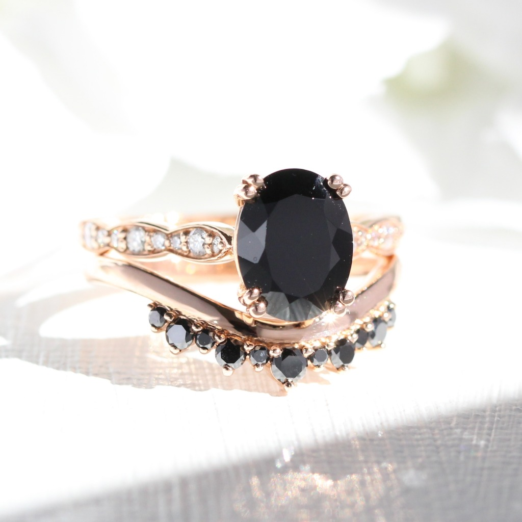Dark and romantic, an Oval Solitaire Black Spinel Engagement Ring in Scalloped Diamond Band paired with a Black Diamond Crown Wedding