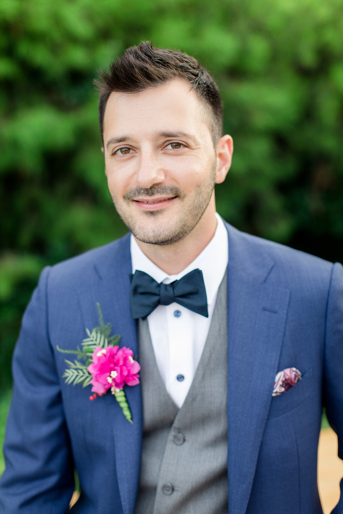 groom in glue suit with grey vest and pink boutonniere