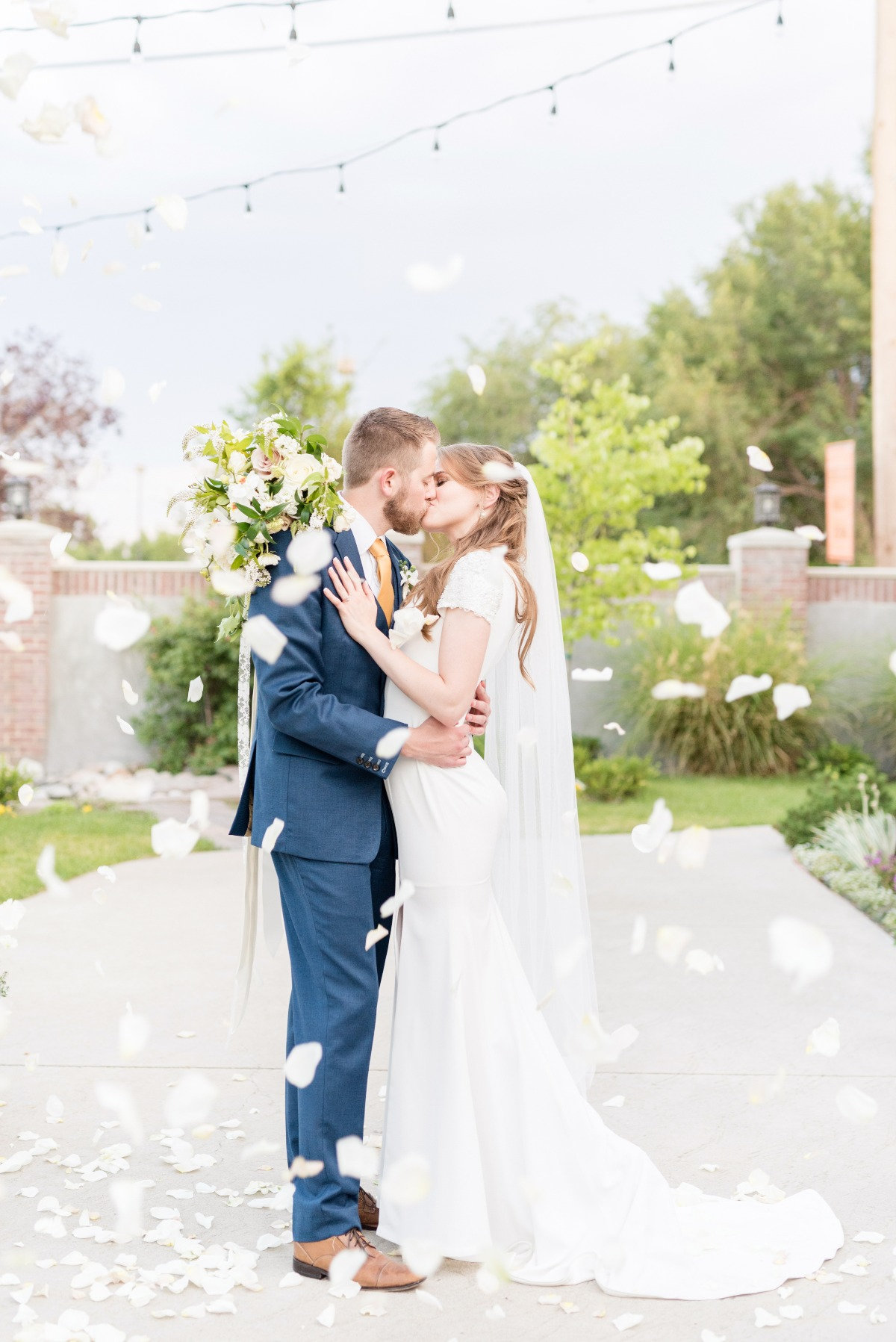 wedding kiss with flower petal toss