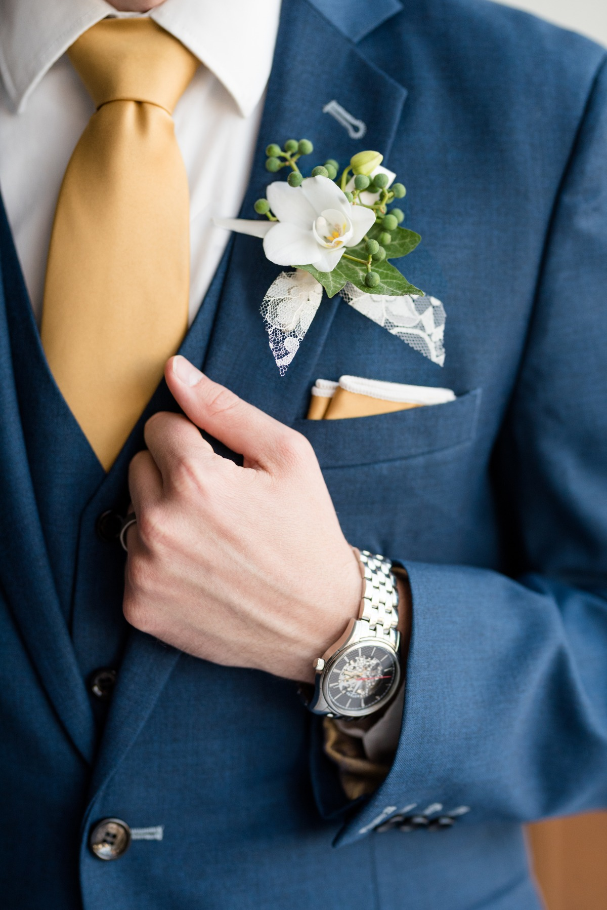 blue suit with gold tie and pocket square groom look