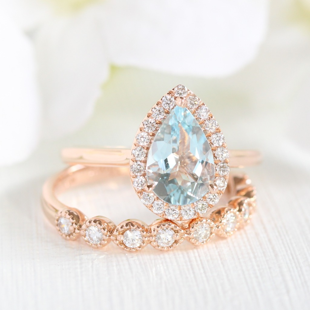 Beautiful Aquamarine Bridal Set featuring pear cut aquamarine surrounding in a halo of diamonds paired with a milgrain half eternity