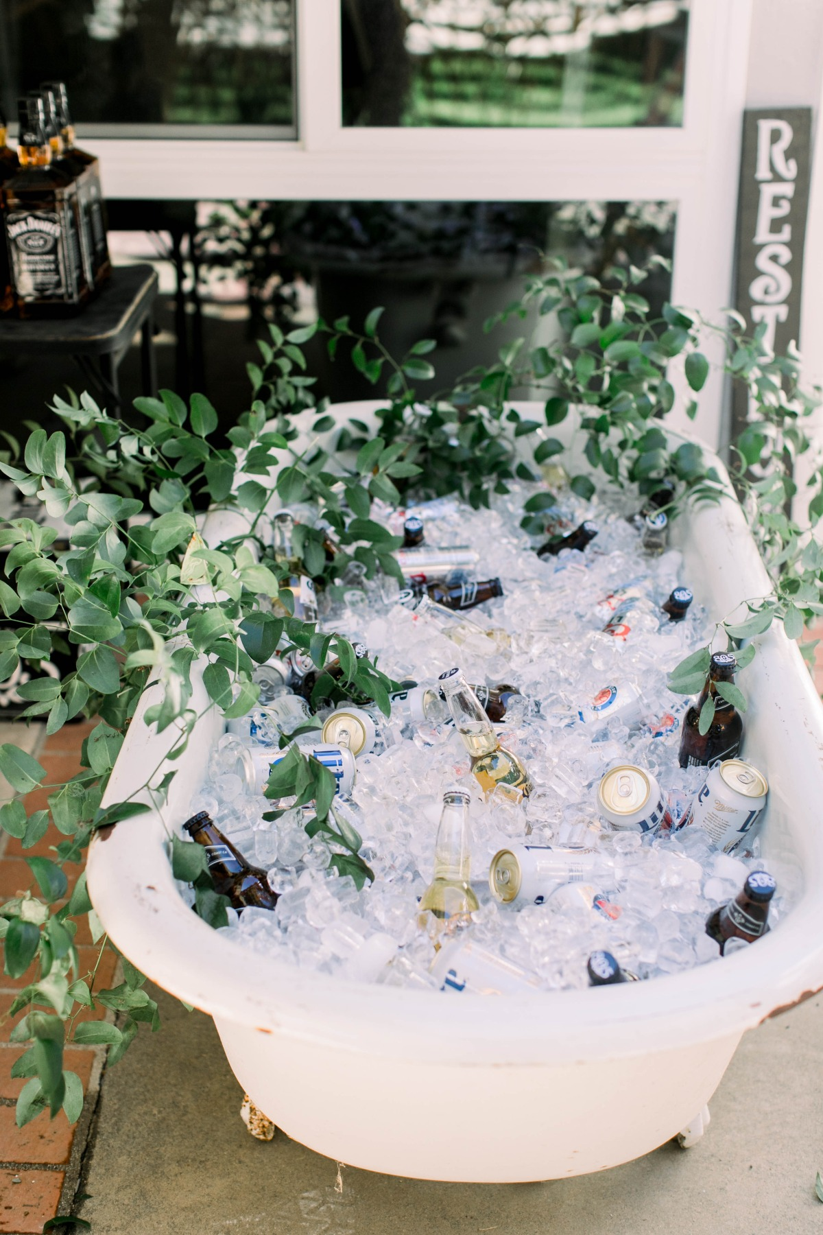 Bath tub cooler for a summer wedding in Tennessee filled with ice and beers, surrounded by greenery