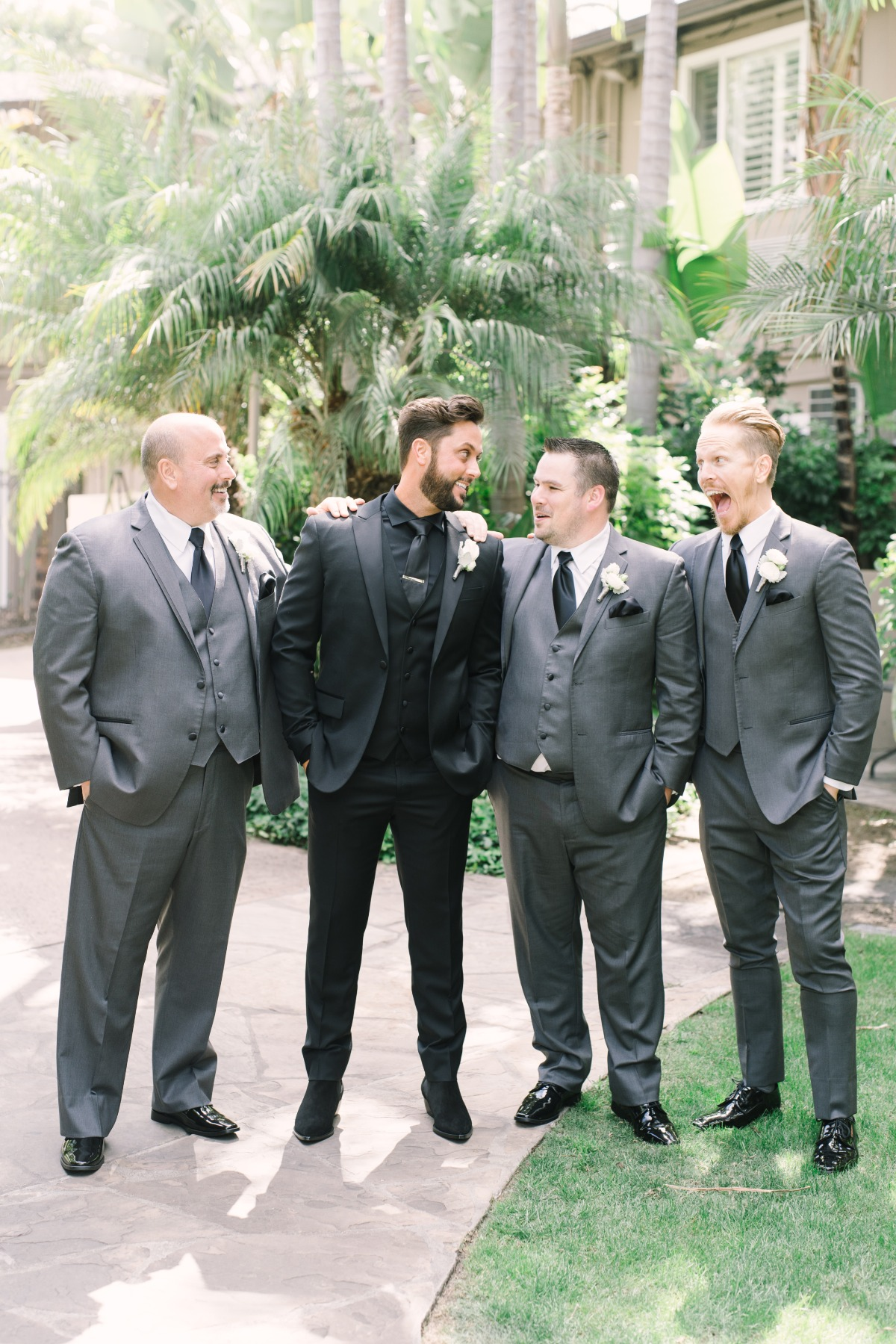 groom in all black groomsmen in grey and black