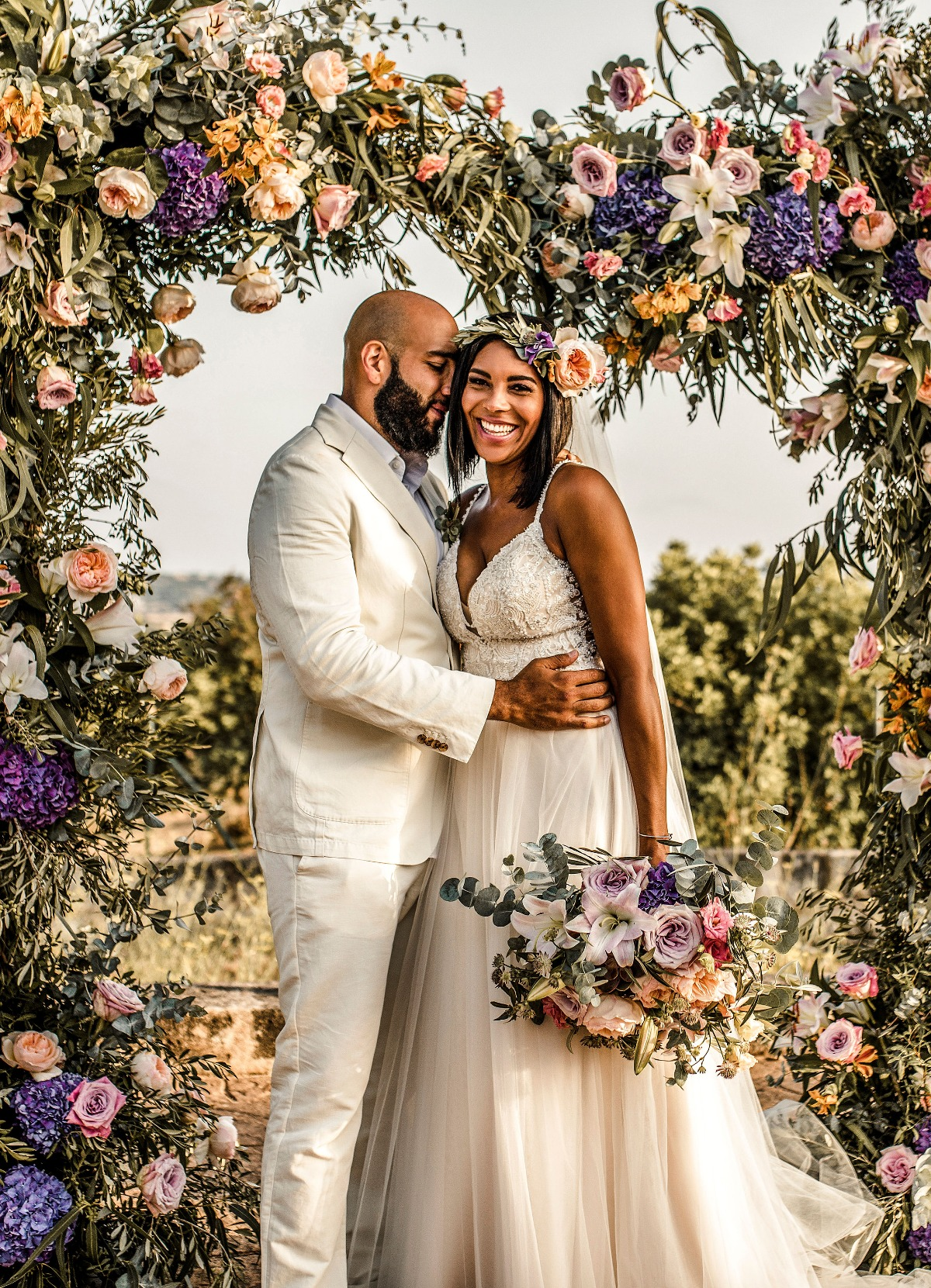 wedding couple with floral arch backdrop
