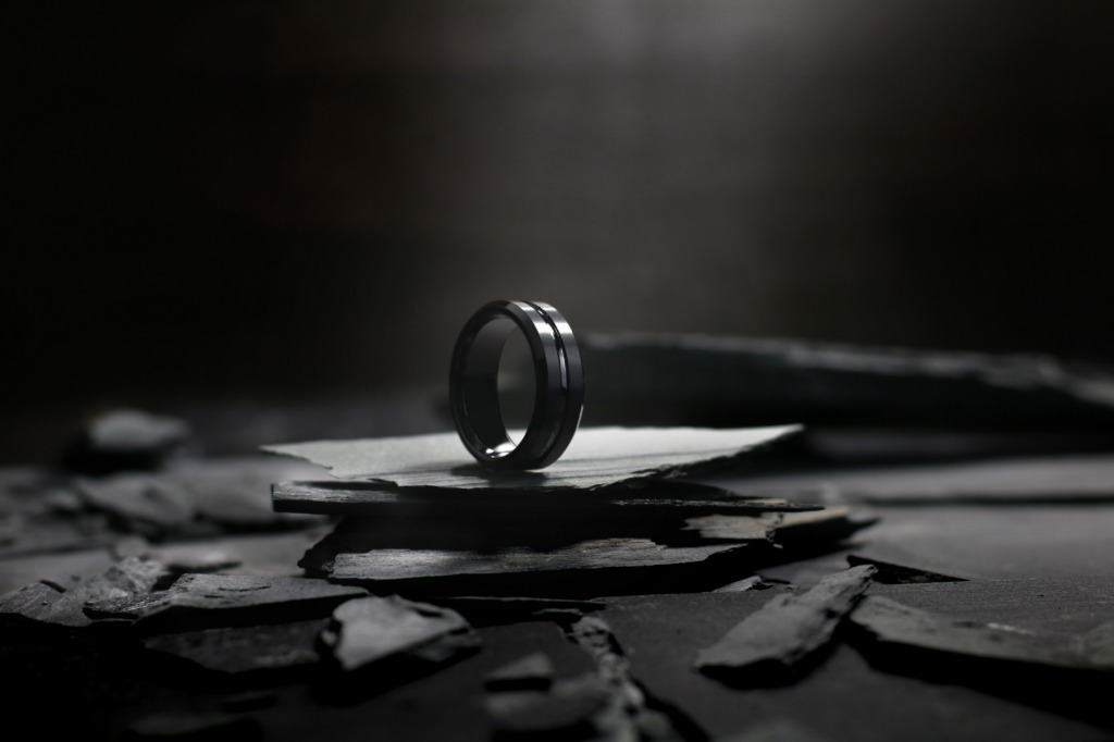 Mens black wedding ring with a carved center channel.