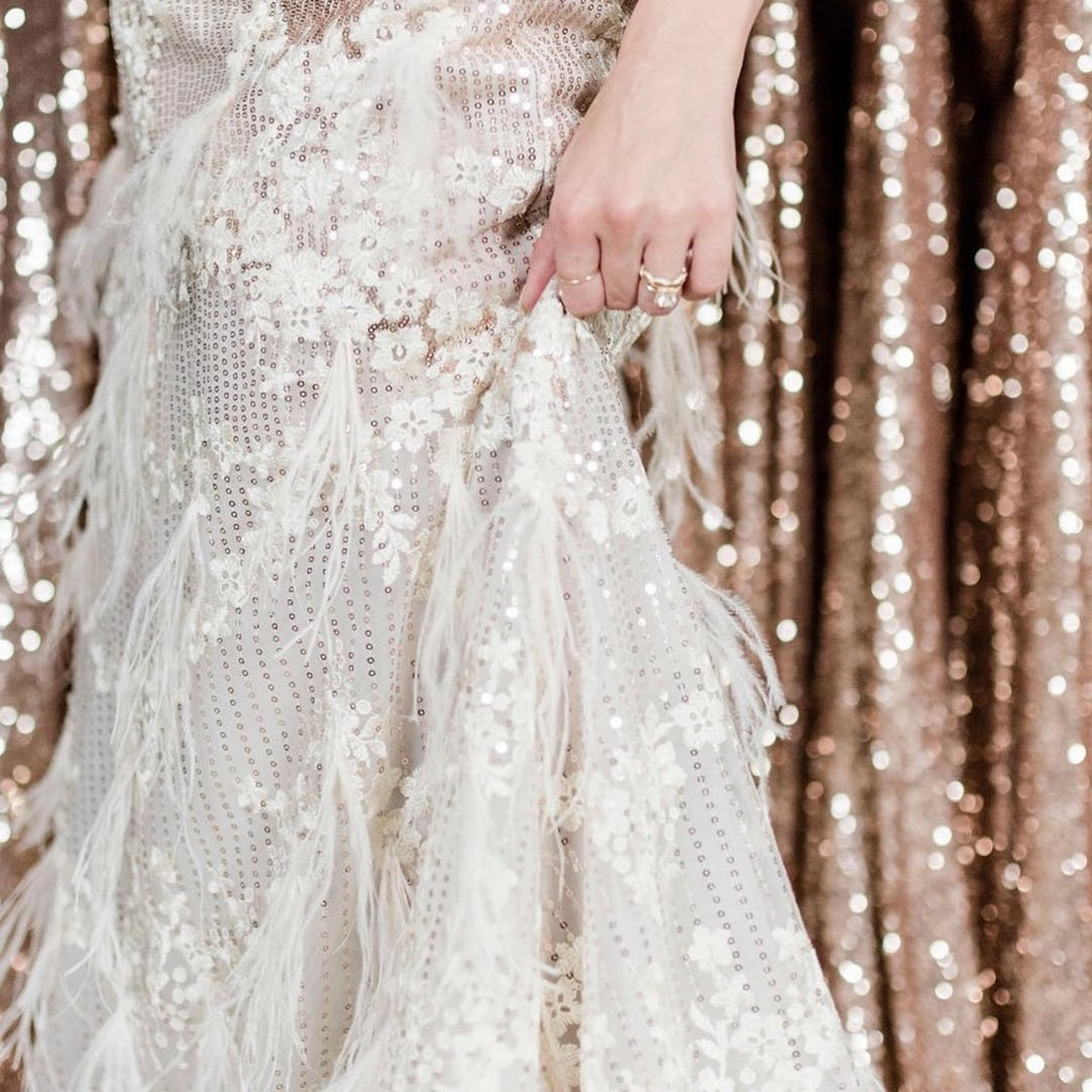 Feathers, sequins, & sparkles, oh my! Our Meesha Bridal Gown pulls out all the stops for the bride who dreams of stunning the night