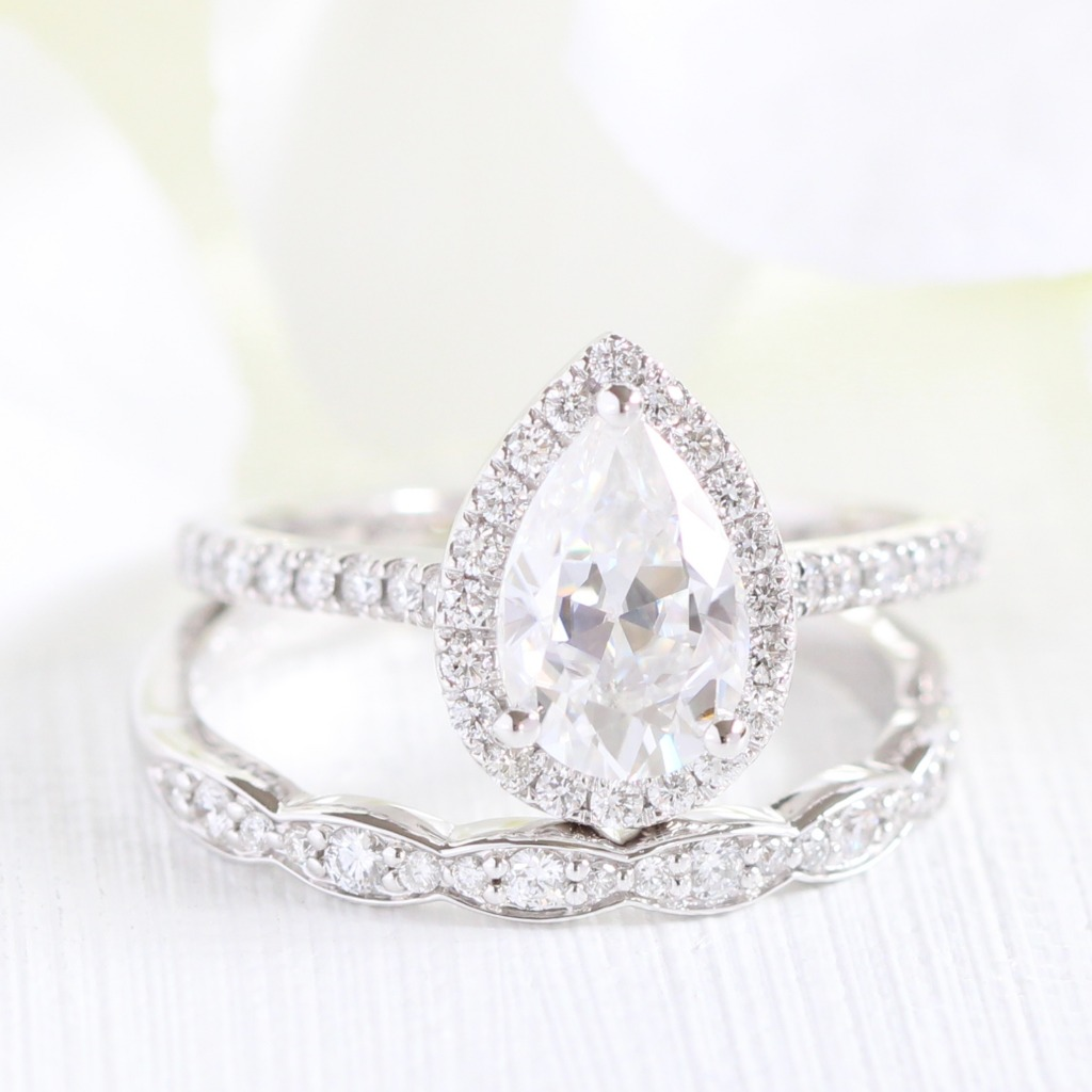 Classic in all white, our Luna Halo Pear Moissanite Engagement Ring pairs beautifully with a vintage inspired scalloped diamond wedding