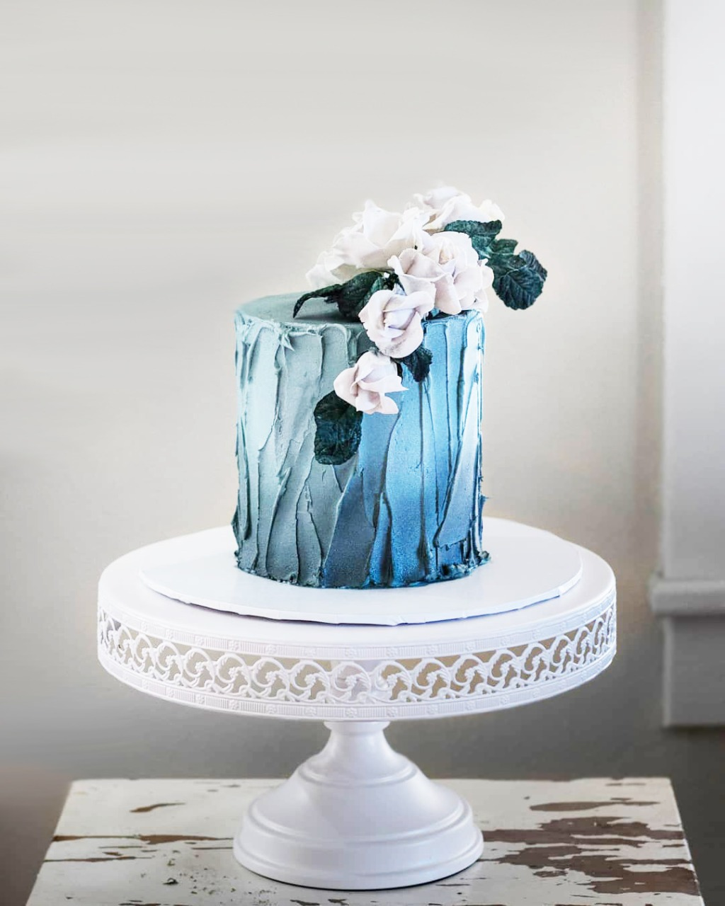 Pretty little something blue wedding cake by @bijoussweettreats on Opulent Treasures white cake stand.