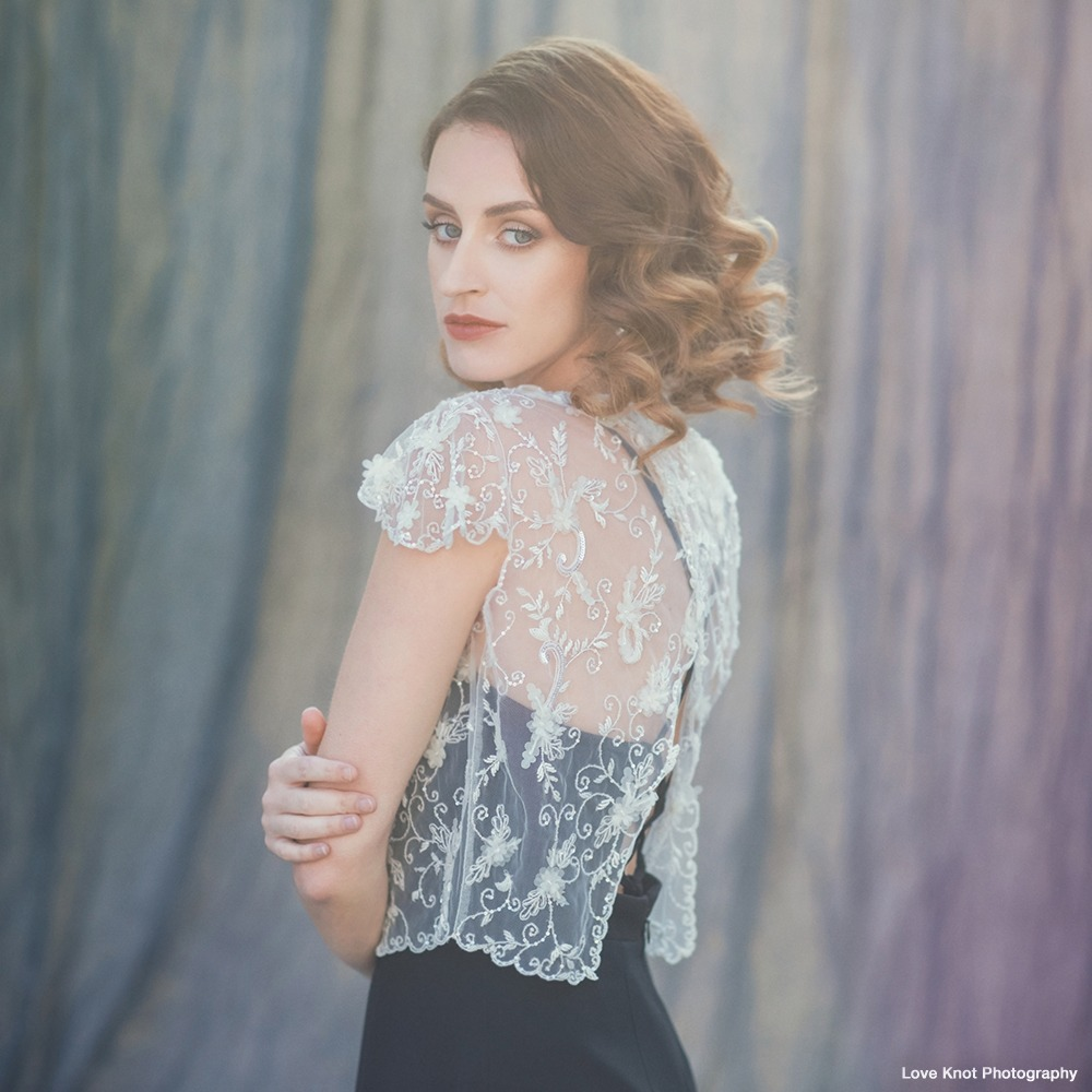 A stunning cover-up with a gorgeous back. Hand-embroidered & beaded with a scatter of soft organza flowers on ivory net. Jewel