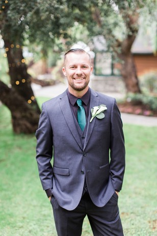 groom in charcoal grey and emerald green