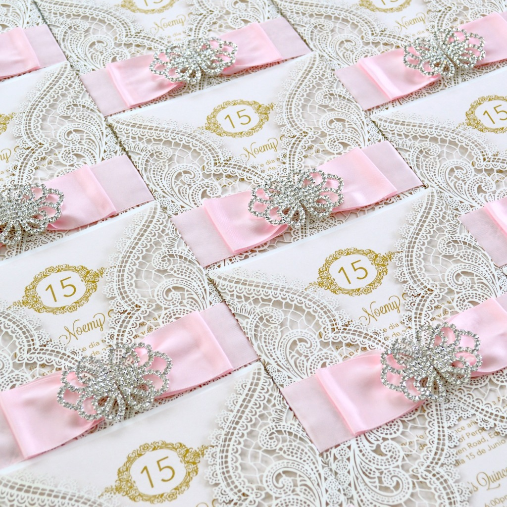 So much glitz and glamour in these Quinceañera invitations. Layering these gate-fold laser-cut invitations with a satin ribbon and