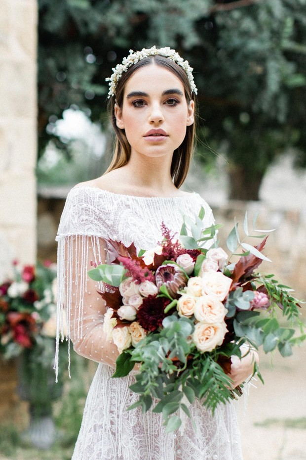bride in elegant dress with peach and burgundy bouquet