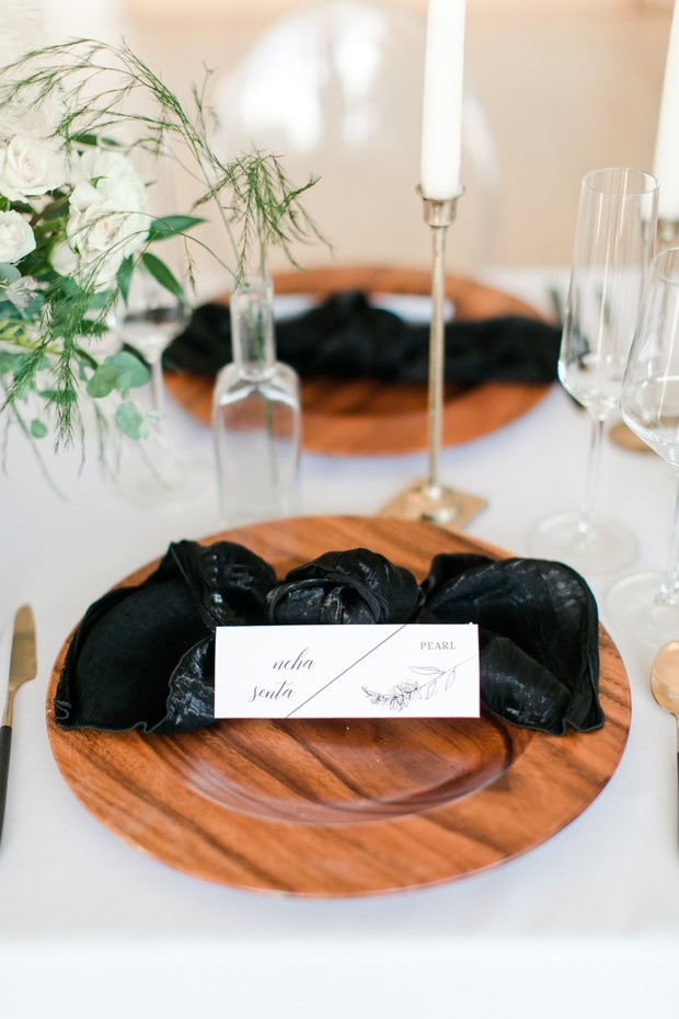 wooden wedding plates with black bow tie tied linens