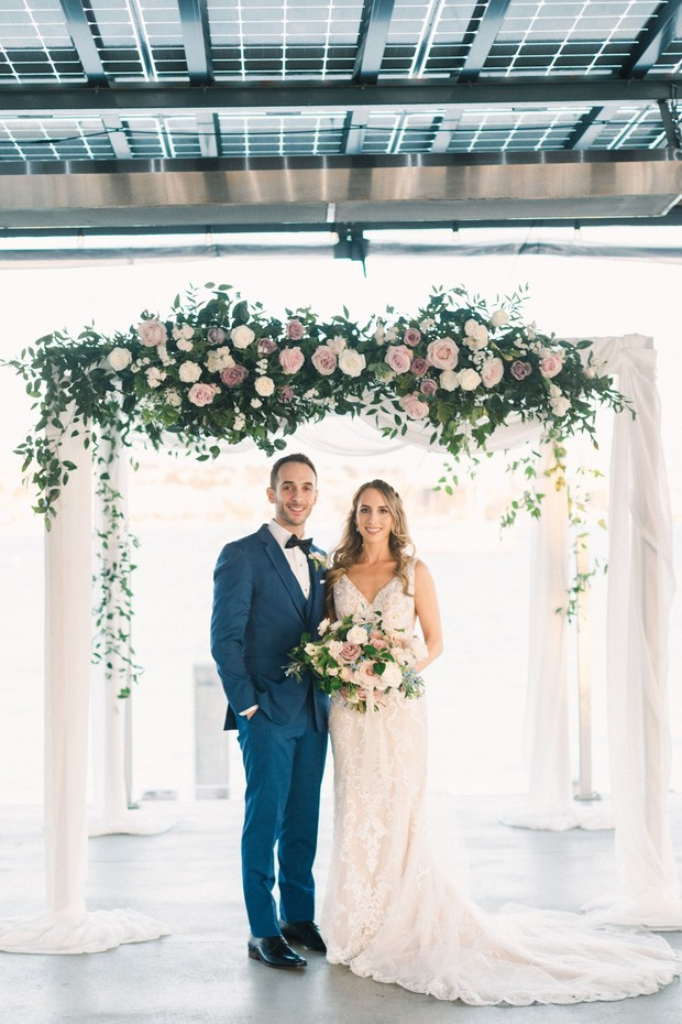 bride and groom with floral accented Chuppah