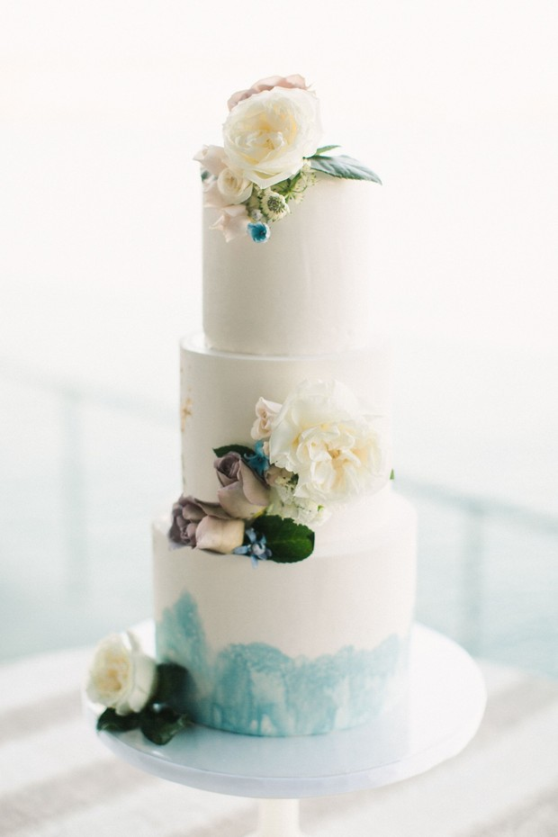 flower topped blue and white wedding cake