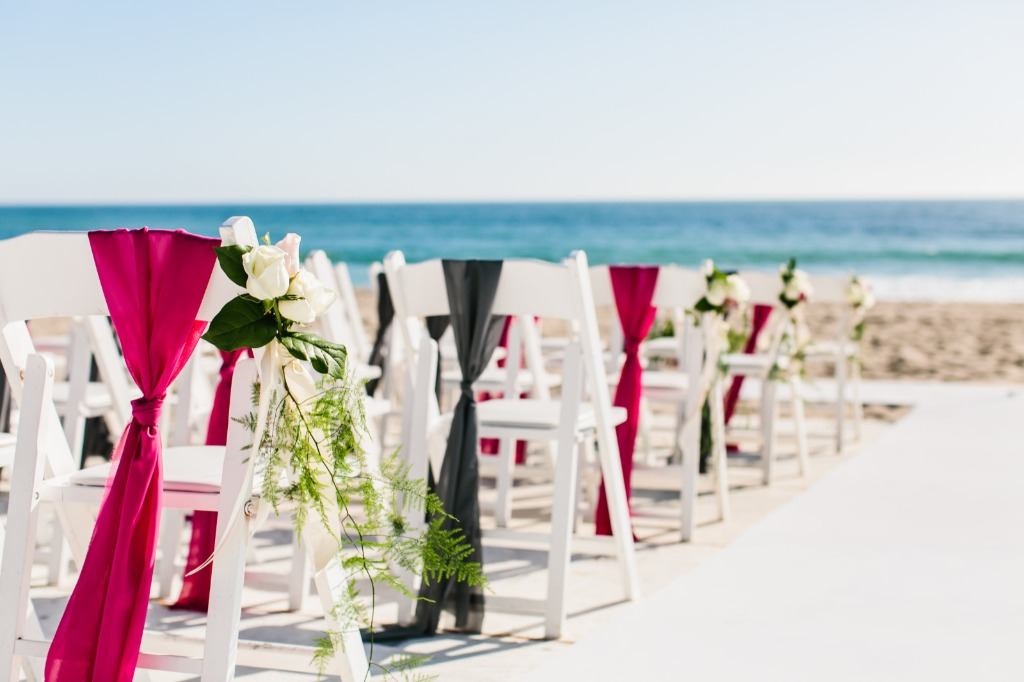 These beautiful fuchsia and grey chiffon sashes were draped on the chairs of this outdoor beach wedding ceremony to add a pop of color