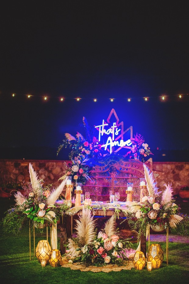 Eclectic boho sweetheart table with neon sign