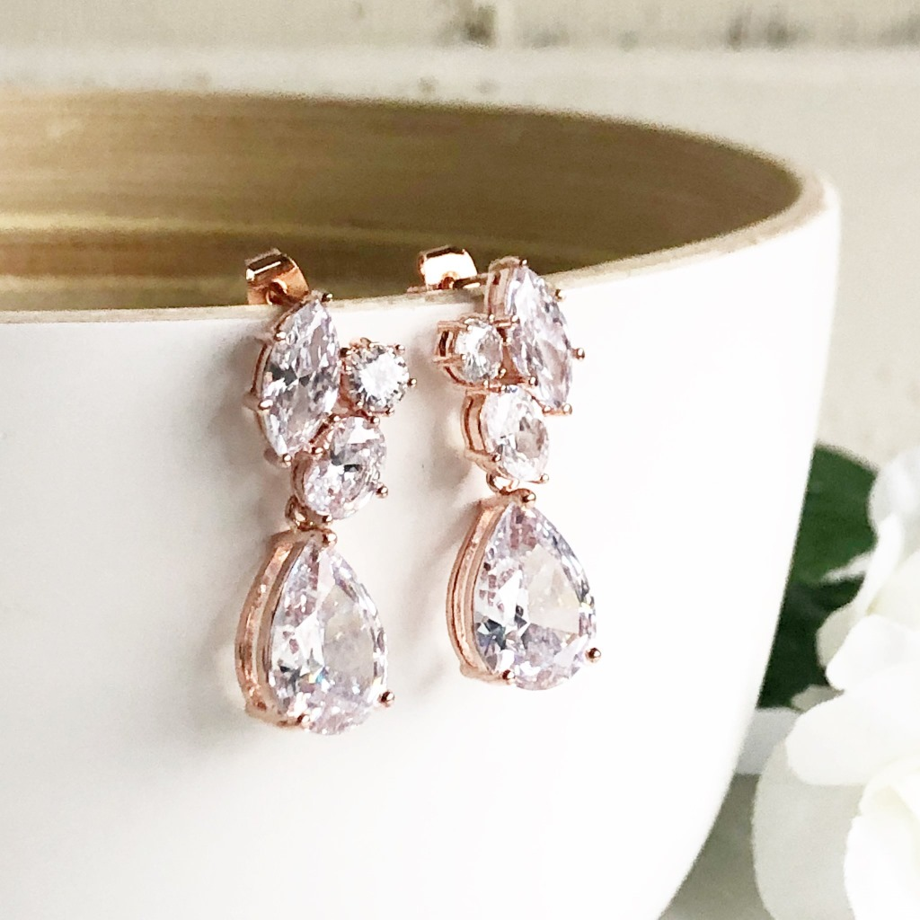 The stones are glass and cublic zirconia set in rose gold plated brass. The earrings are about 1.35 long.