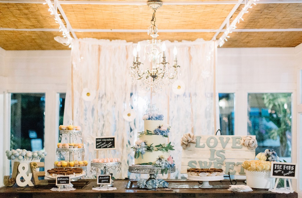 Wedding dessert table featuring pie pops, mini cupcakes, chocolate gems, and cake pops with a tiered textured buttercream wedding cake