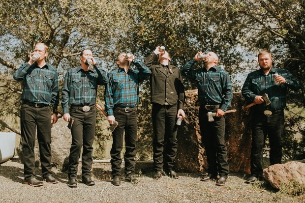 groomsmen in flannel with beers and axes