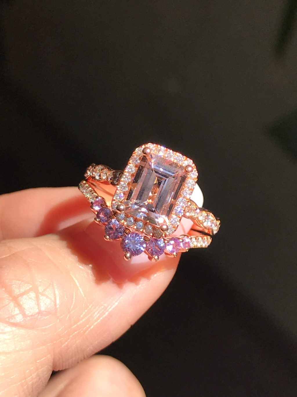 Peach and purple meet and fall in love in this Emerald Cut Morganite Halo Diamond Engagement Ring with Curved 7 Stone Purple Sapphire