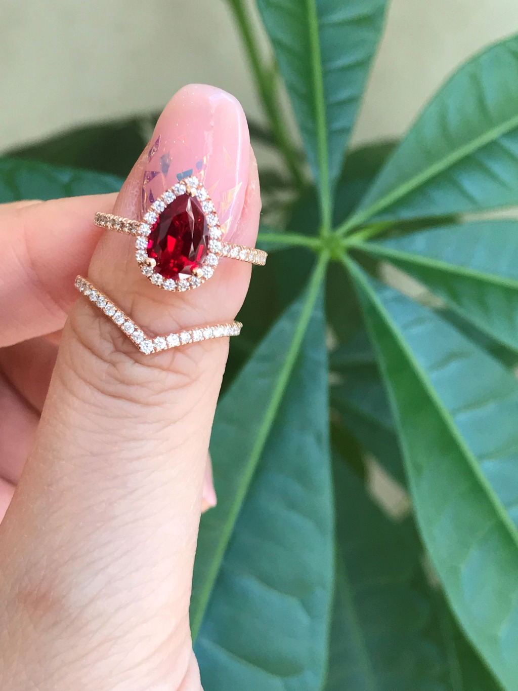 This stunning bridal ring set features a 9x6mm Pear Cut Ruby surrounded by sparkling conflict free natural white diamonds set in 14k