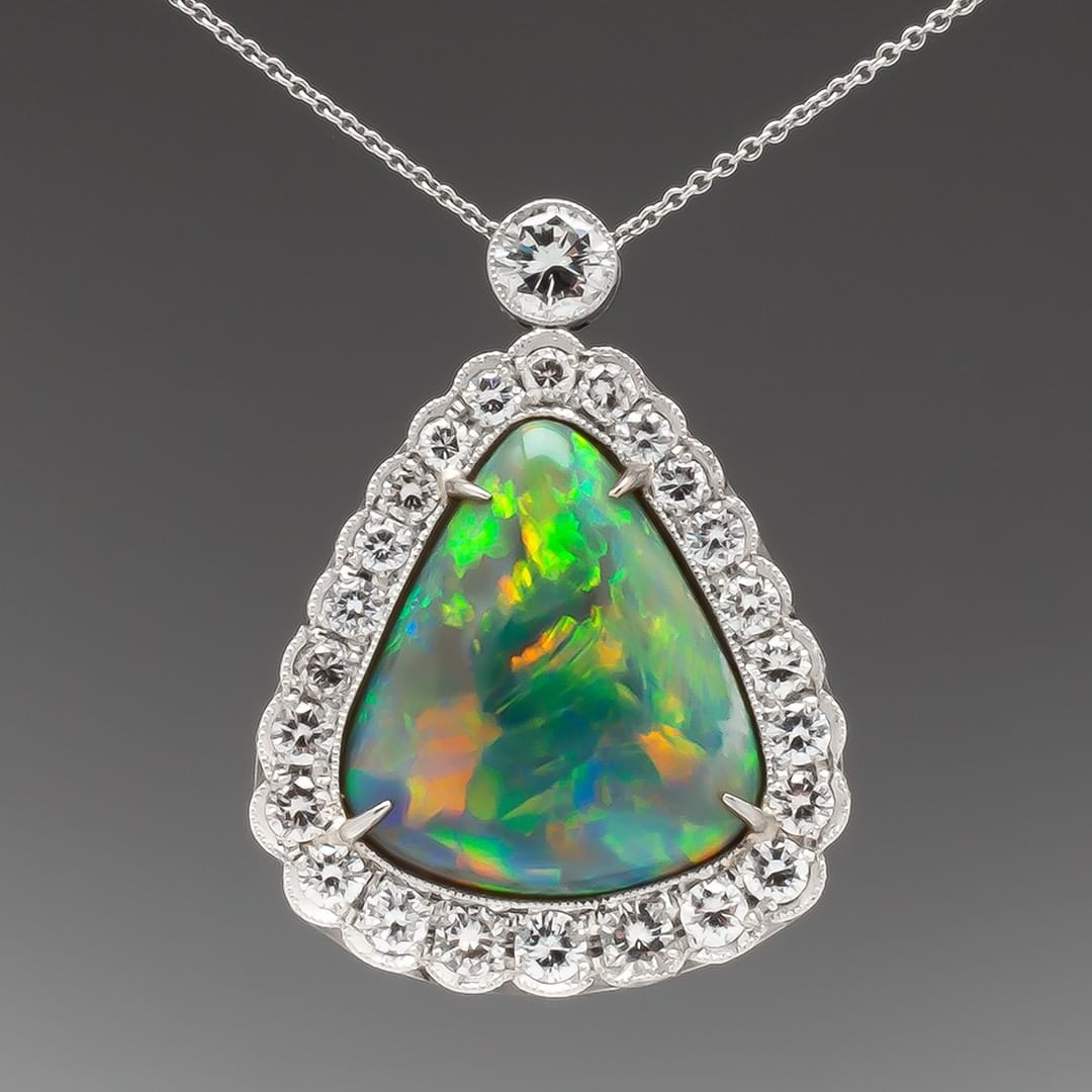 This large and amazing black opal is surrounded by diamonds and milgrain detailing. It drops from a lovely bezel set diamond bale,